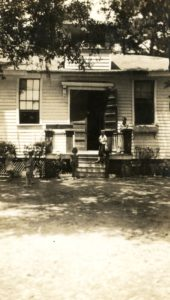 A photo of James Island Grammar School in 1938. Shows a young boy and a woman standing on the steps.