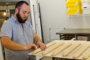 Baker Jesse Murray prepping baguettes for baking. Photo by Liz McCafferty.