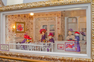 "Tony Jones' miniature creation Red Hat Shop, features a fictitious chapter of the Red Hat Society ""The Palmetto Plumes""  enjoying tea time in the shop."