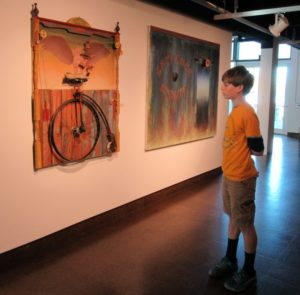 Boy viewing one of the art pieces.