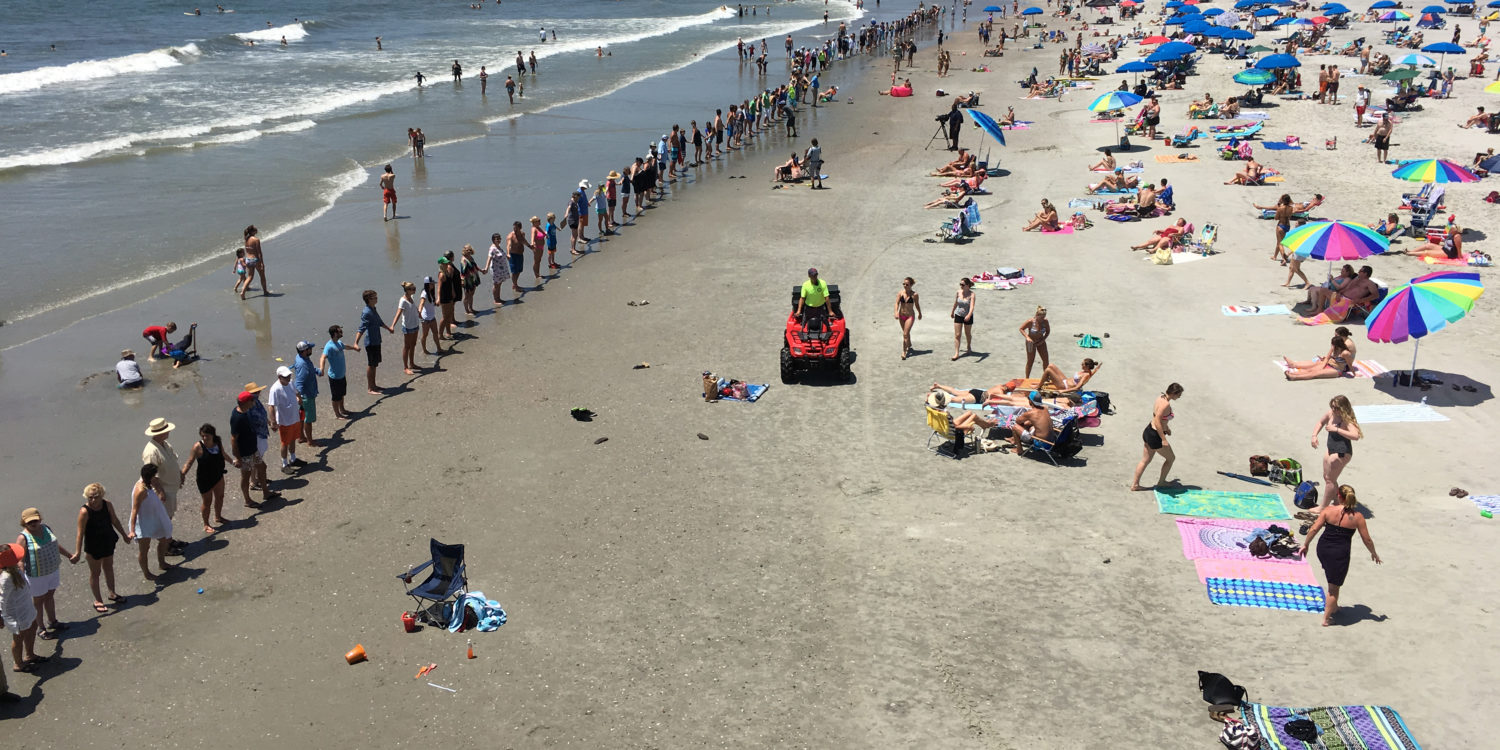 People standing hand in hand on Folly Beach for Hands Across the Sand